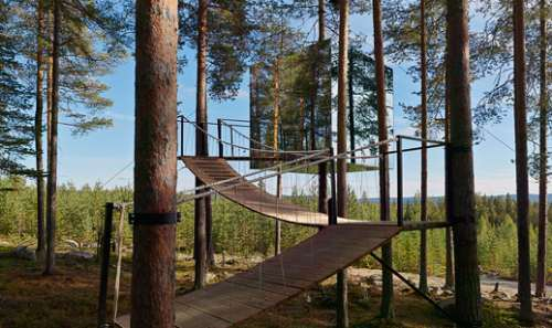 Homesthetics Conclusion:  The level of transparency and reflectiveness allows this particular design to perfectly integrate into the chosen environment.By mimesis it becomes one with the canopy of trees, offering its guests an unique natural experience. Photo courtesy to Tham & Videgård Arkitekter interior modern design minimalsit design shape furniture wooden latter climbing to hotel