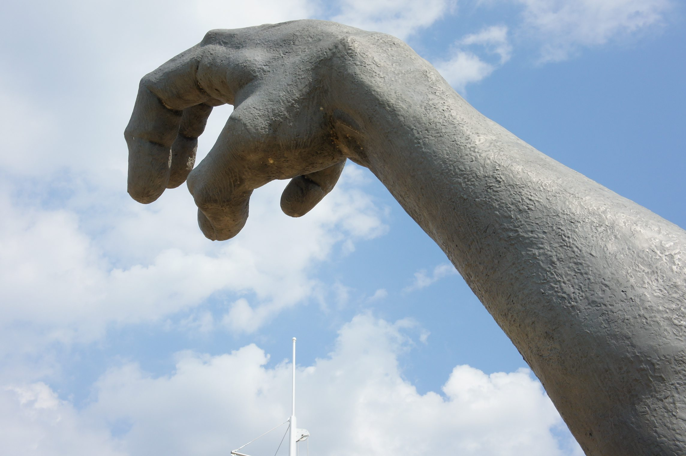 J. Seward Johnson Jr screaming statue contemporary art installation sculpture on sandy beach rising from the earth close-up of the hand