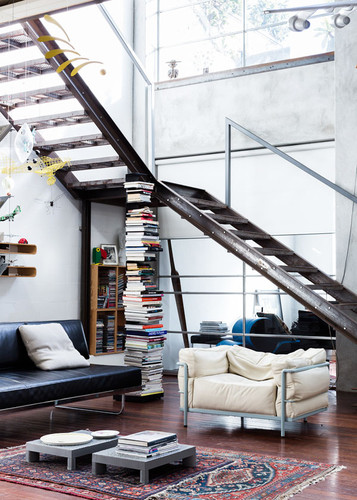 extraordinary staircase sustained by bookcases in a very well illuminate living room interior design