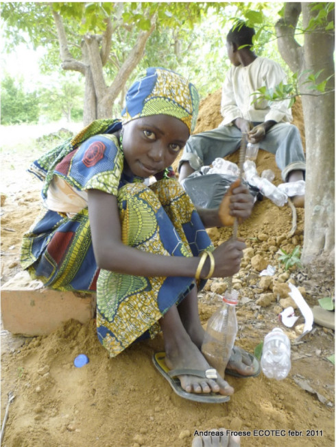 african child working on Experimental Living- Sustainable Plastic Bottle House by D.A.R.E (1)