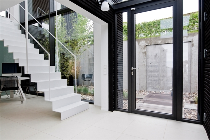 staircase flowing in white stark on the Nilsson Villa-Modern Beach House With Black and White Interior Design in Sweden