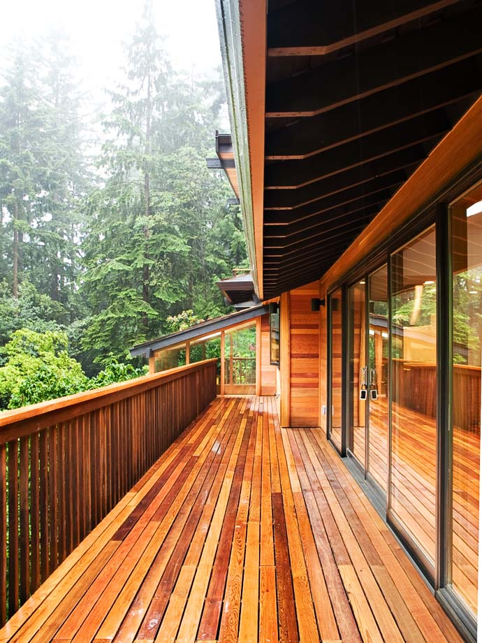 exterior balcony wrapped in wood Green Modern Classic House by PLACE Hidden in the Forest