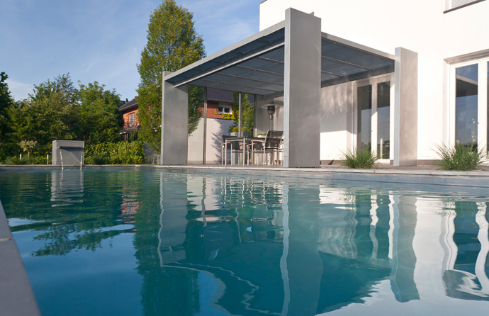 the reflection of a house in a swimming pool