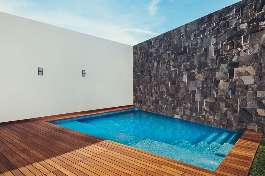 Private Pool with a Wooden Deck and a Stone Wall