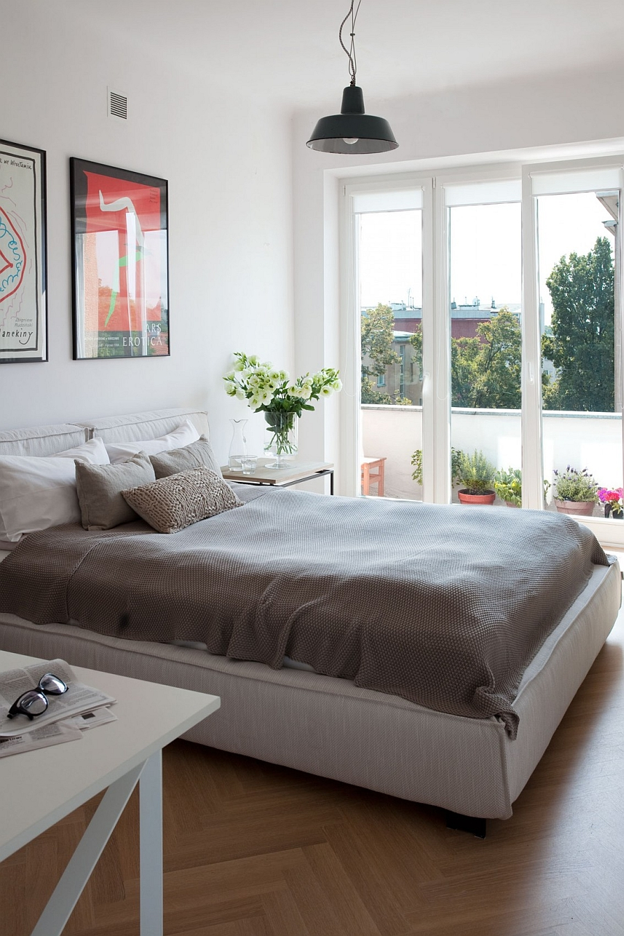 Bedroom in White Connected With the Balcony Outside Through Huge Windows Emphasizing the Feel of Space