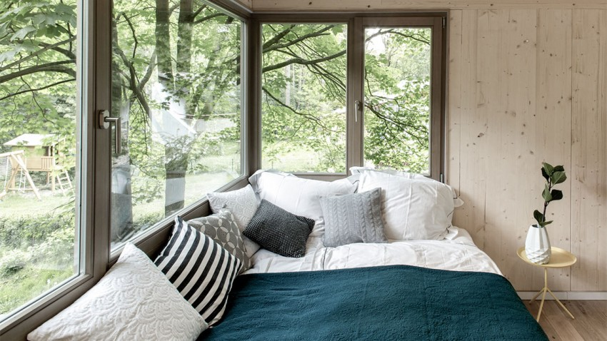 corner bedroom window allowing expansive views in the forest