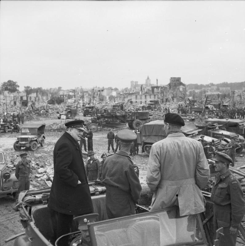 The allies victorious among the ruins of Caen , Winston Churchill on the left wearing a suit and cap and on the right , standing up against the window of the staff car , none other than Field Marshal Montgomery.