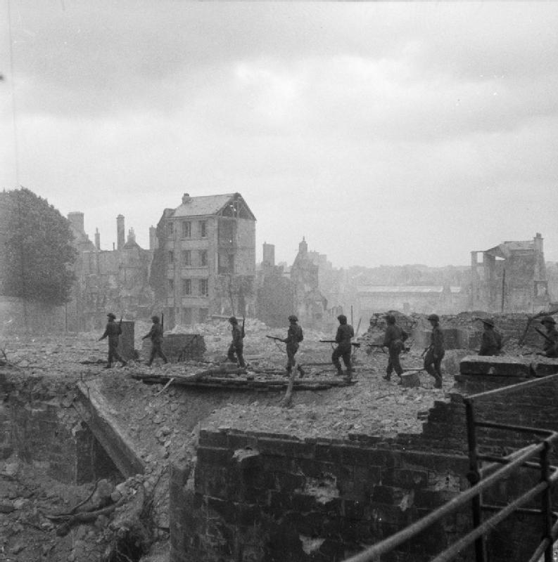 Allied soldiers in the ruins of Caen
