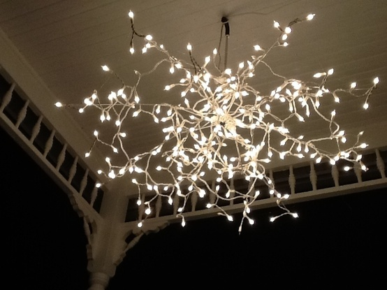 25. Recycle on old metallic umbrella body and a string of of shimmering lights for a flower chandelier