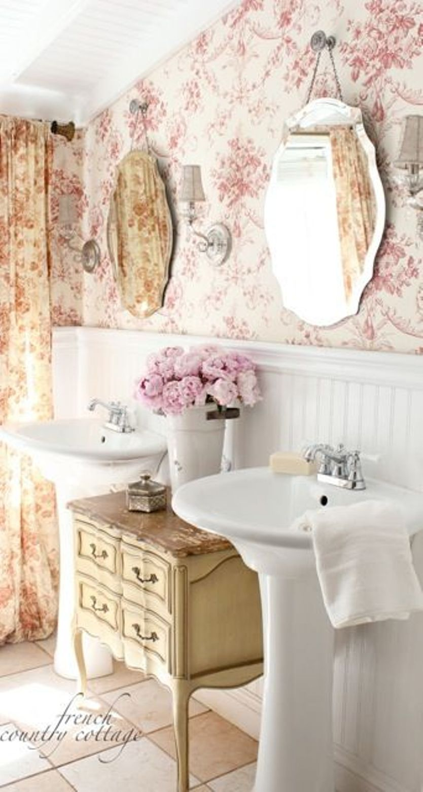 small-bathroom-makeovers-with-wainscoting-and-wallpaper-and-vintage-cabinet-between-two-pedestal-sinks-and-mirrors-and-flower-style-curtain