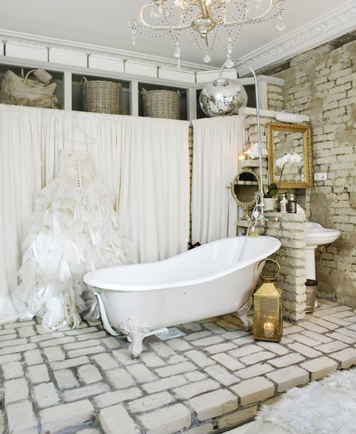 vintage-bathroom-theme-idea-with-brick-wall-and-floor-and-clawfoot-tub-and-crystal-chandelier-and-white-curtains-and-baskets