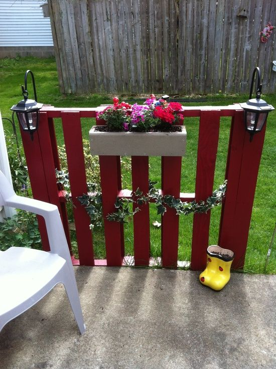 #1 A SMALL PATIO FENCE HOLDING GREENERY AND FLOWERS IN A PLANTER