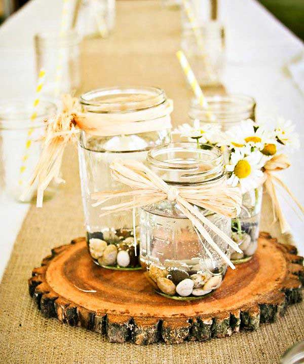 #17 Mason Jars Filled With Rocks and Water Filled With Flowers on a Slice of Wood