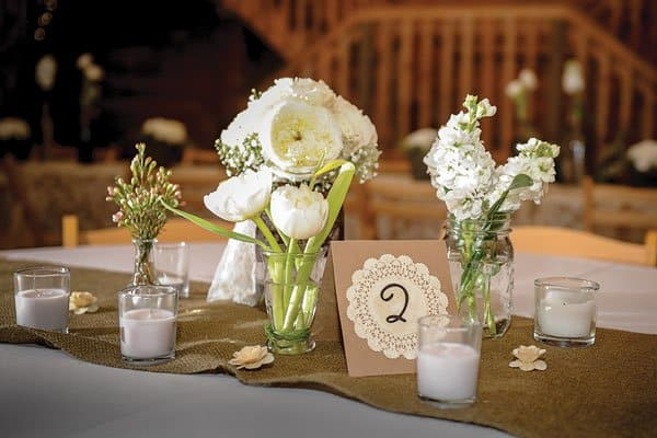 #17 mason jars and candles along a jute table runner might be beautiful and delicate enough