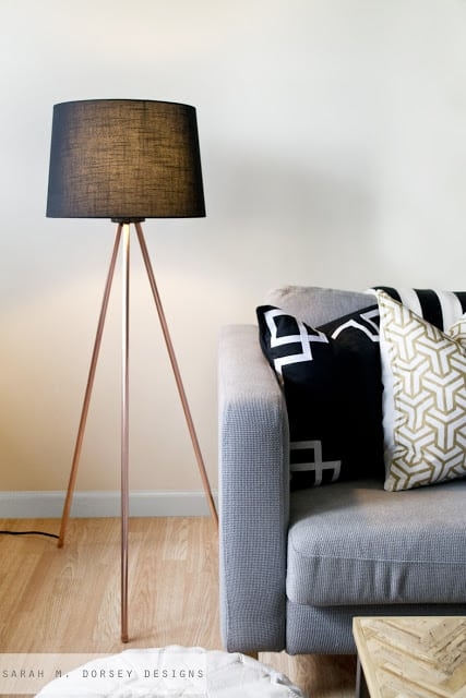 A DECORATIVE COPPER TRIPOD FLOOR LAMP