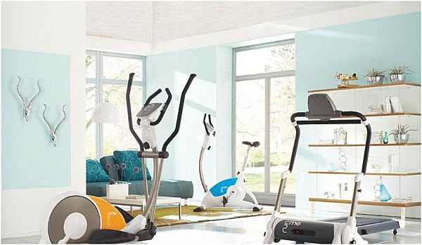 Light blue and white airy gym design with plush seating area.