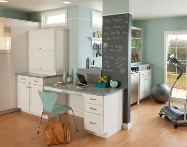 Tiny multipurpose area containing laundry room, office and home gym.