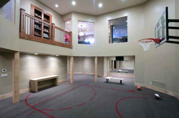 Impressive home gym in the basement with carpeted basketball courtyard