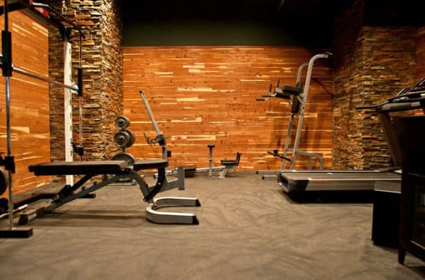 Custom rubber flooring and cedar wool walls tailored with stone in an interesting home gym composition.