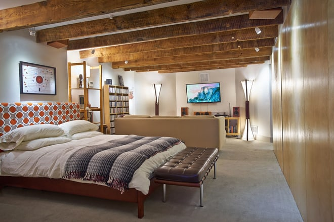 exposed wooden beams enhancing a basement bedroom