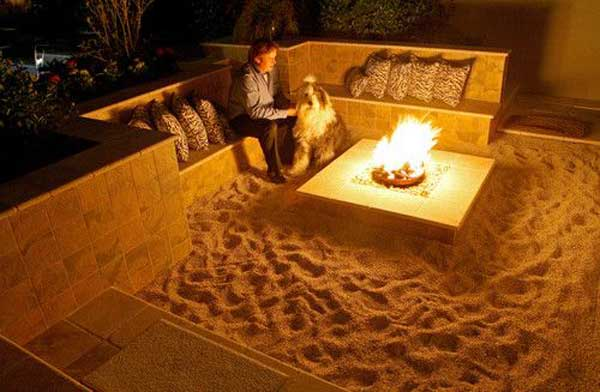 SUNKEN SITTING AREA WITH SAND FLOORS WARMED BY A FIRE PIT