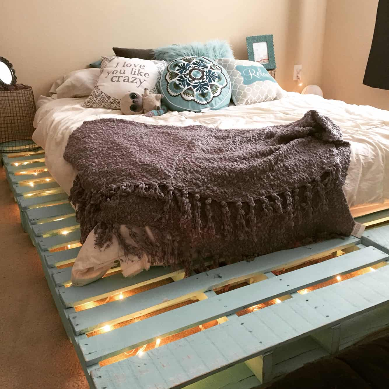 7. DELICATE PASTEL TURQUOISE PALLET BED FRAME LIT BY STRING LIGHTS