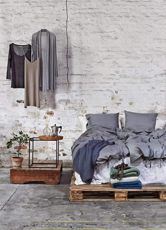 16. RAW INDUSTRIAL LOFT DESIGN WITH EXPOSED BRICK WALLS, CEMENT FLOORING AND PALLET BED FRAME