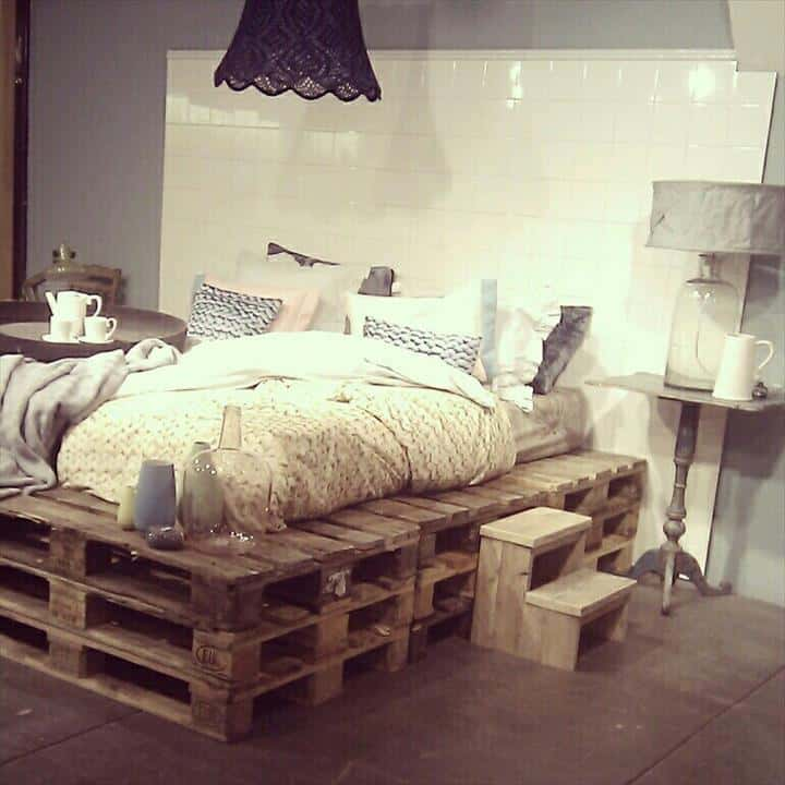 1. LAYERED PALLET FRAME BED WITH A WHITE TILE BACKGROUND SERVING AS A HEADBOARD