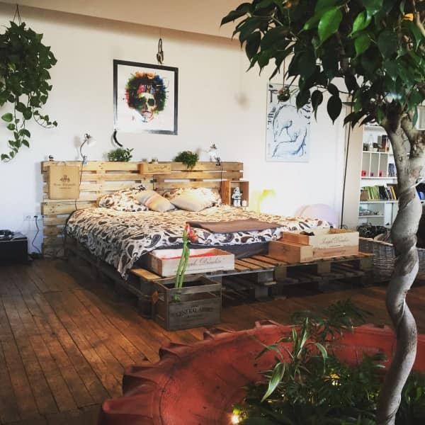 6. A BOHO-CHIC ATMOSPHERE INTEGRATING A PALLET BED FRAME AND GREENERY