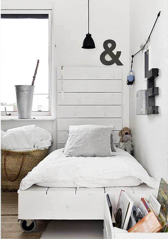 29. A SMALL NARROW PALLET BED ON WHEELS
