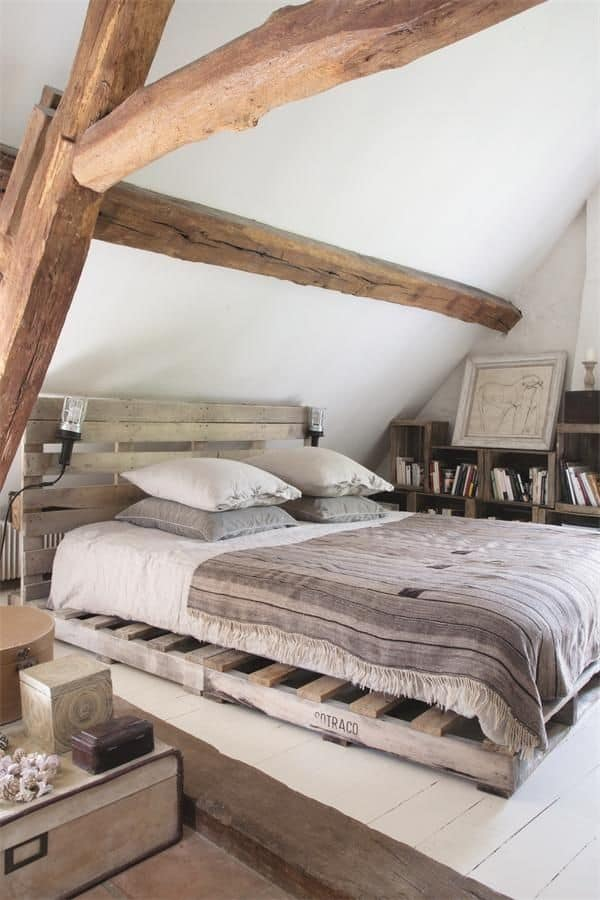 PALLET BED FRAME NESTLED IN A SMALL ATTIC BEDROOM WITH EXPOSED BEAMS