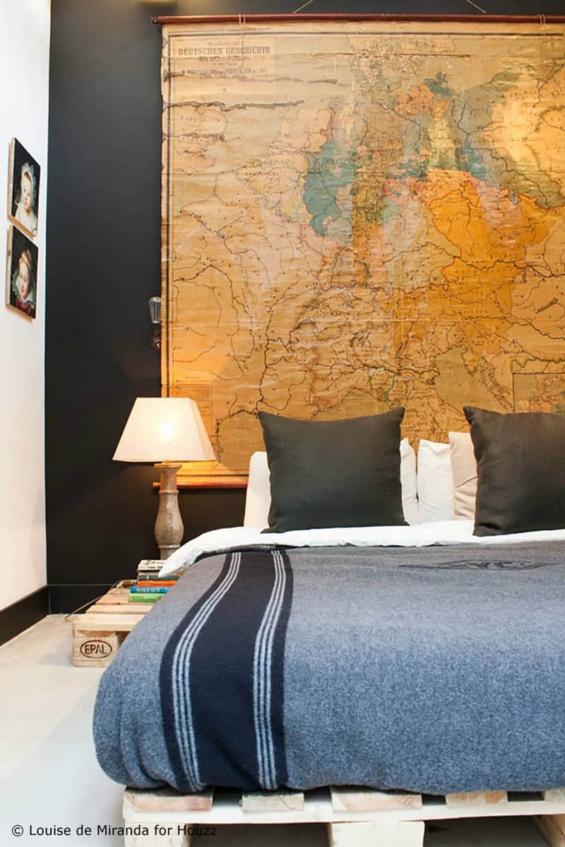 SIMPLE PALLET BED FRAME WITH A LARGE VINTAGE MAP SERVING AS ITS BACKGROUND