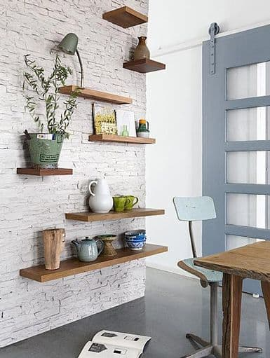 wooden shelves on white brick wall
