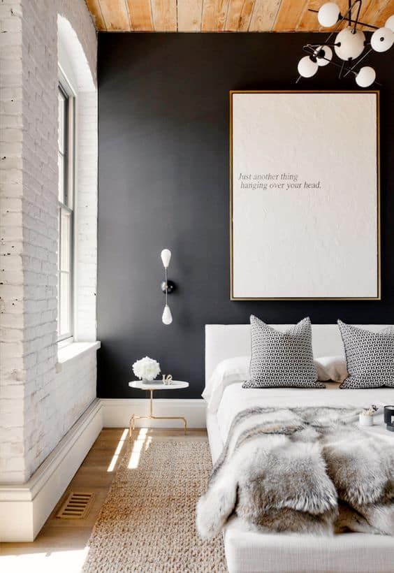 matte black wall contrasts with white brick wall and wooden ceiling