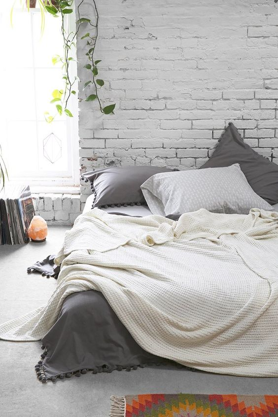 shabby chic industrial bedroom with white brick wall