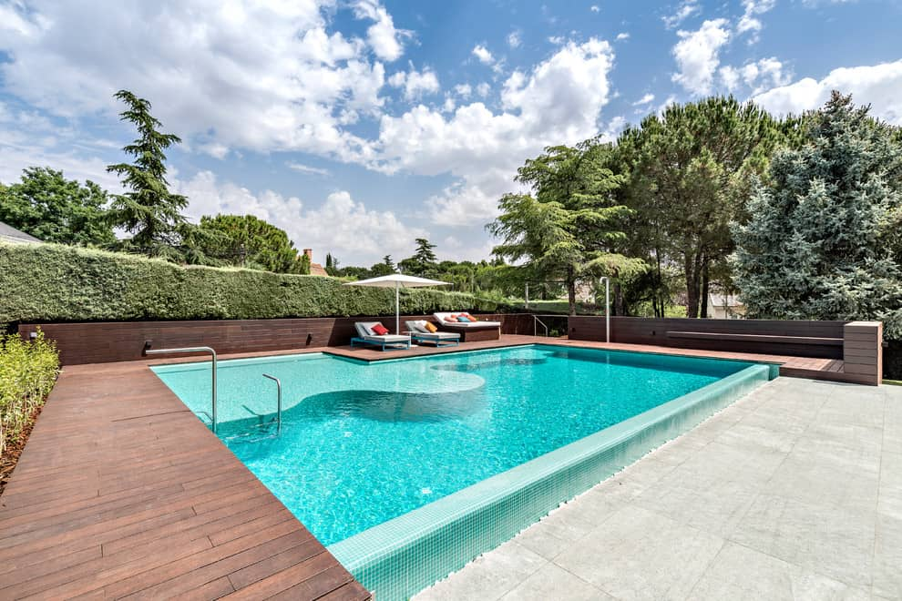 Contemporary Swimming Pool Design With A Lovely Deck And Patio In Madrid