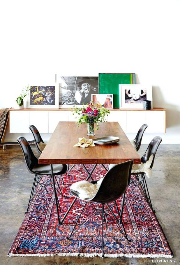 an industrial and modern dining space with leaning artwork persian rug and wood dining dining furniture rug under dining table pinterest modern dining