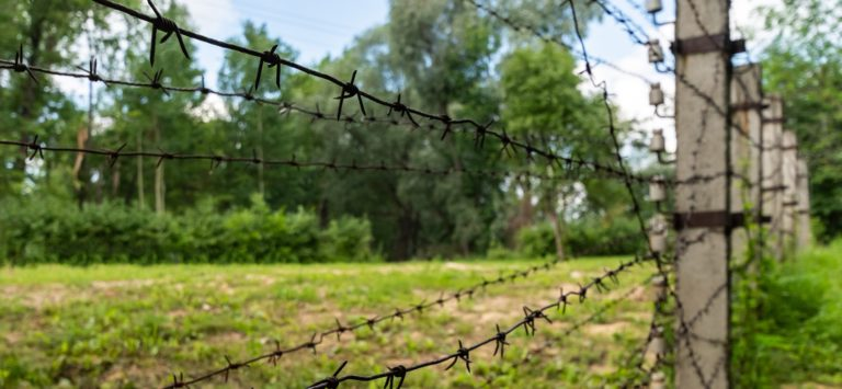 High voltage barbed wire. Private restricted area behind the fence. Old barbed wire.