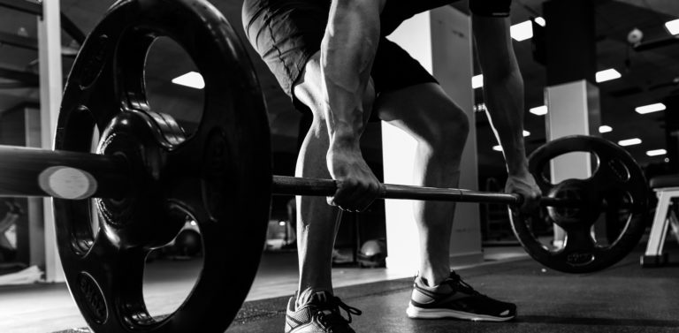 Closeup of weightlift workout at the gym with barbell. Man wearing sportswear clothes.