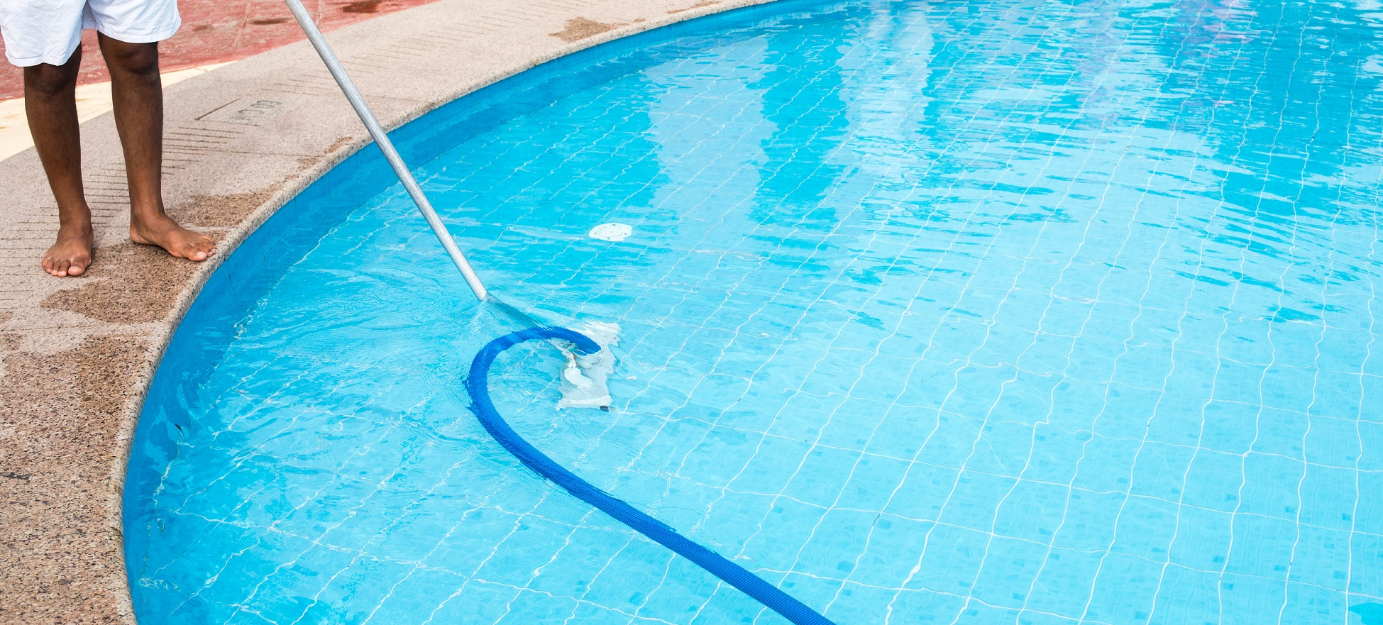 Man cleaning a swimming pool in summer. Cleaner of the swimming pool.