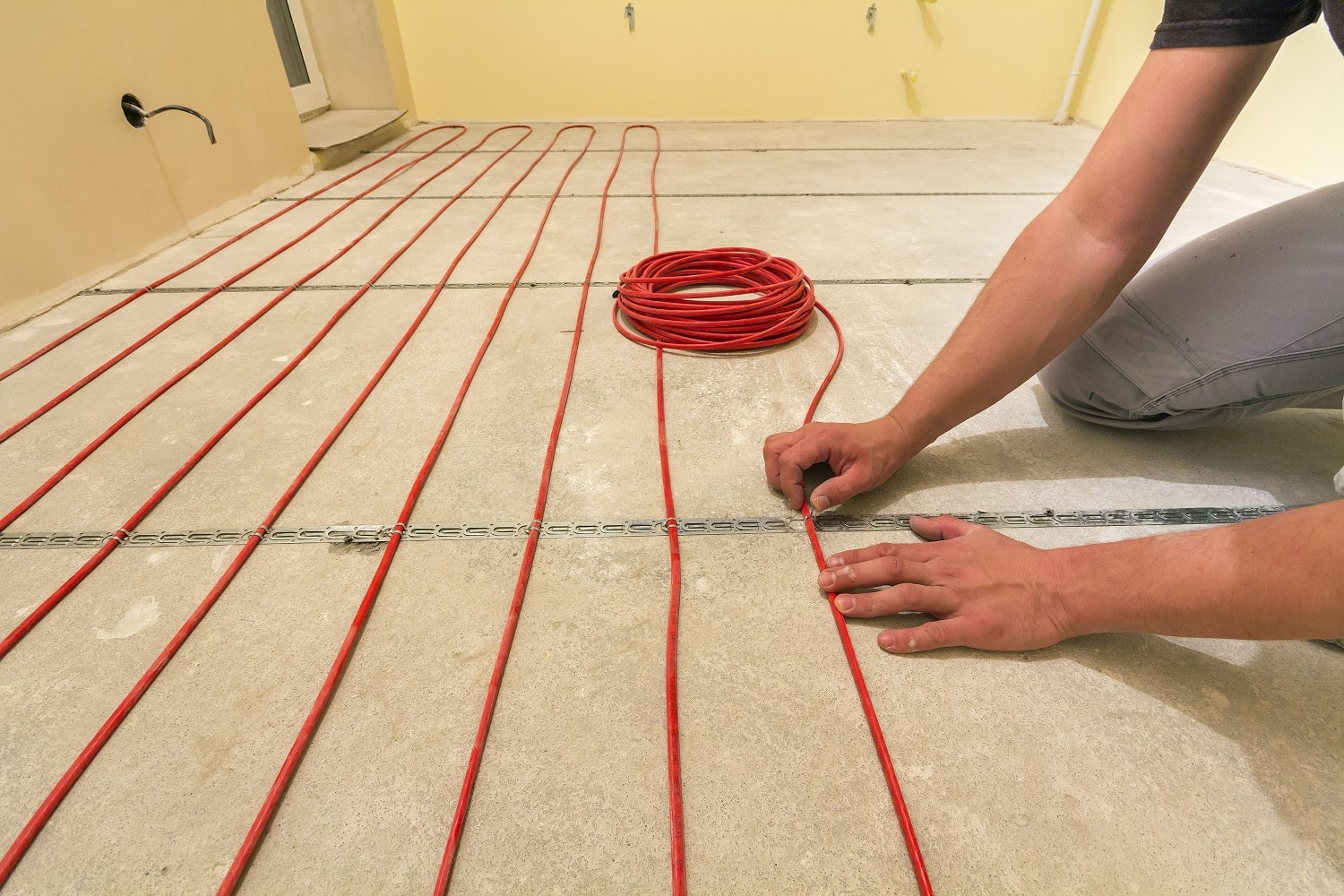 Electrician installing heating red electrical cable wire on cement floor in unfinished room. Renovation and construction, comfortable warm home concept.