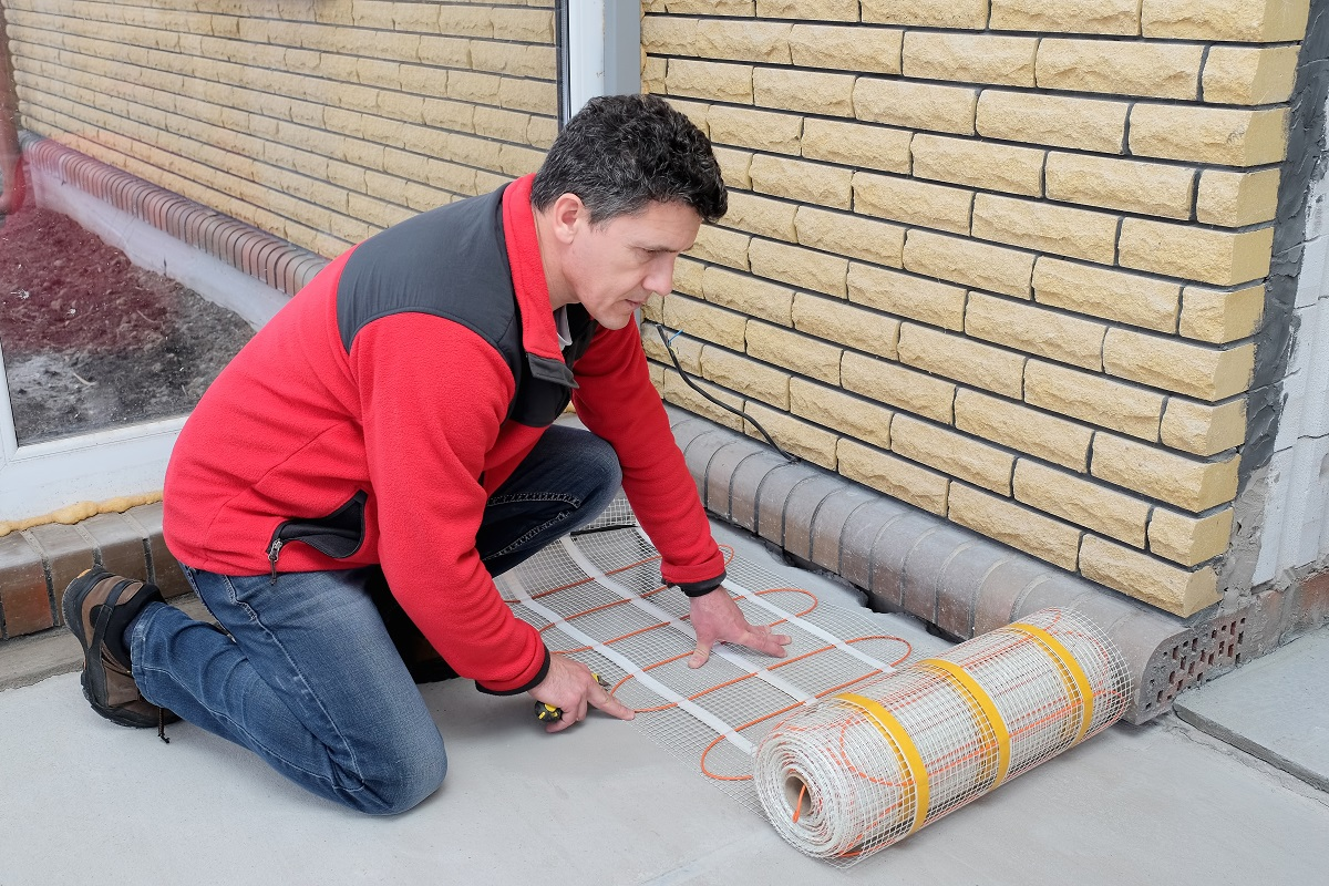 Electrician installing heating electrical cable on cement floor. energy-saving technologies for home comfort