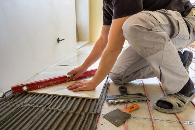Young worker tiler installing ceramic tiles using lever on cemen