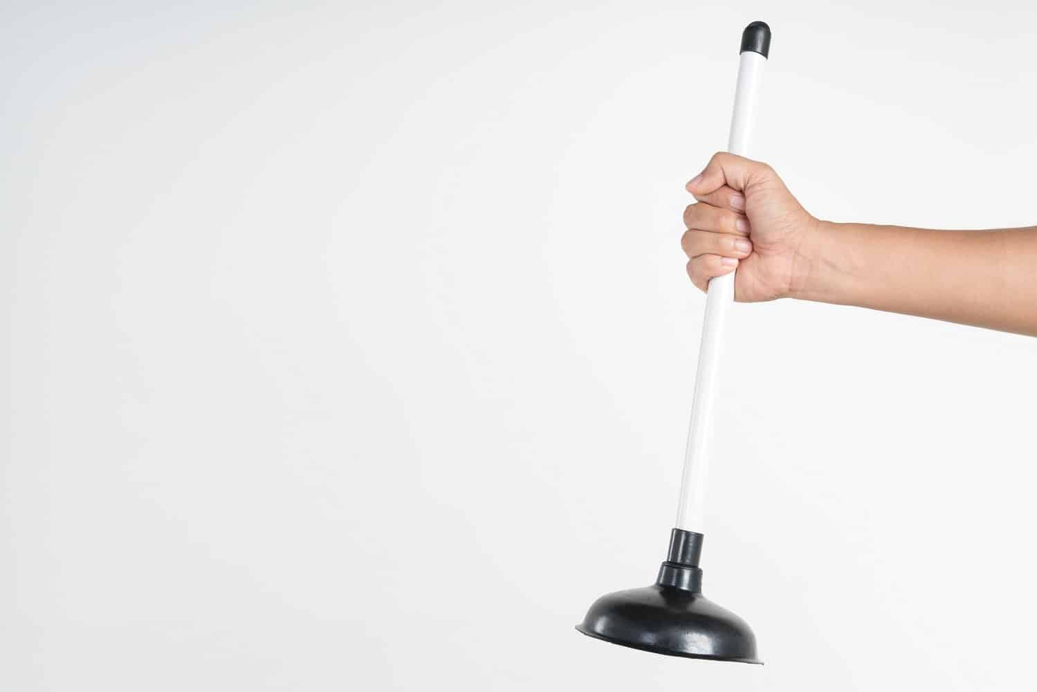 Hand holding toilet black rubber plunger or toilet suction cup for unclog water pipe on white background