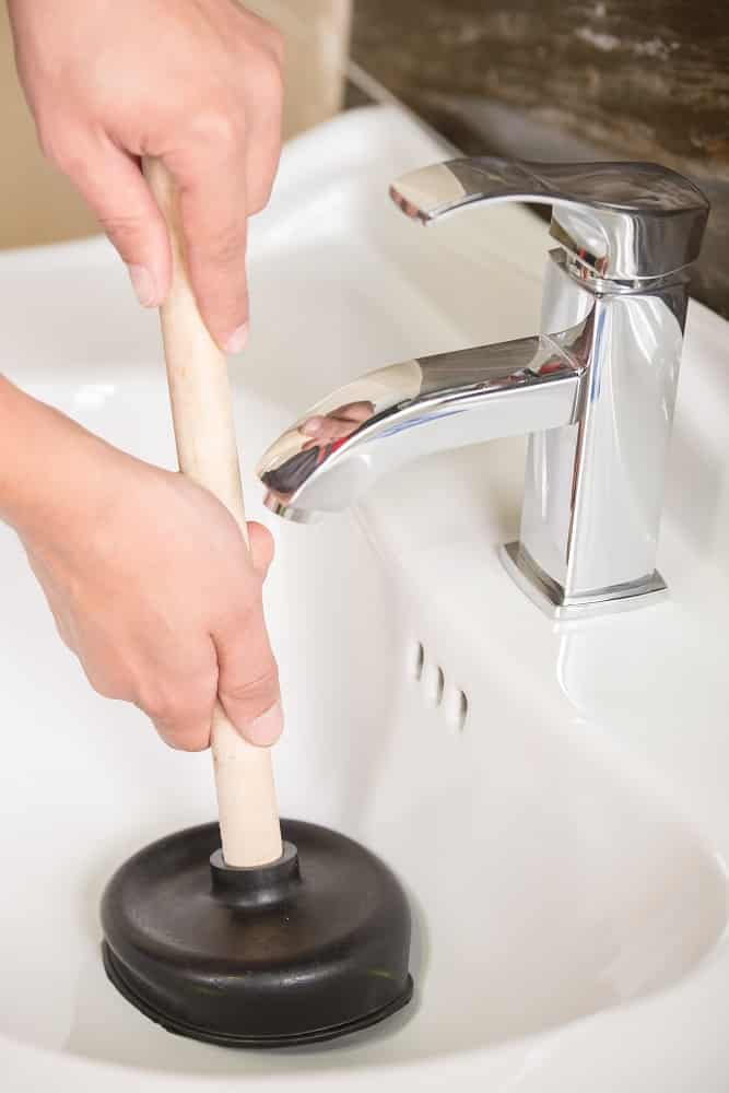 Plumber is cleaning sink with plunger.