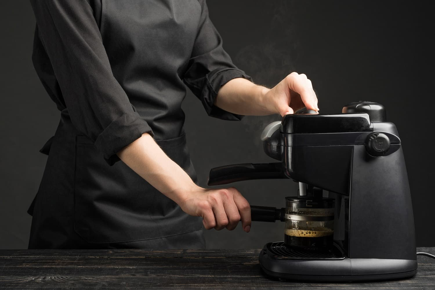 Professional barist with a coffee machine, brews coffee. Against a dark background