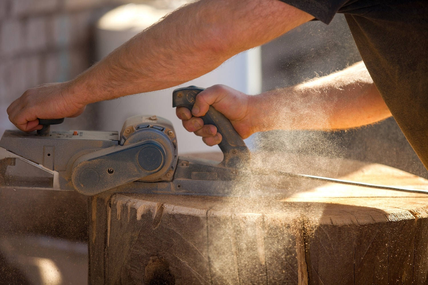 Carpenter working with an electric planer on a wooden STUMP in the open air. man treats wood plane. working joiner aligns the surface. carpenter's work