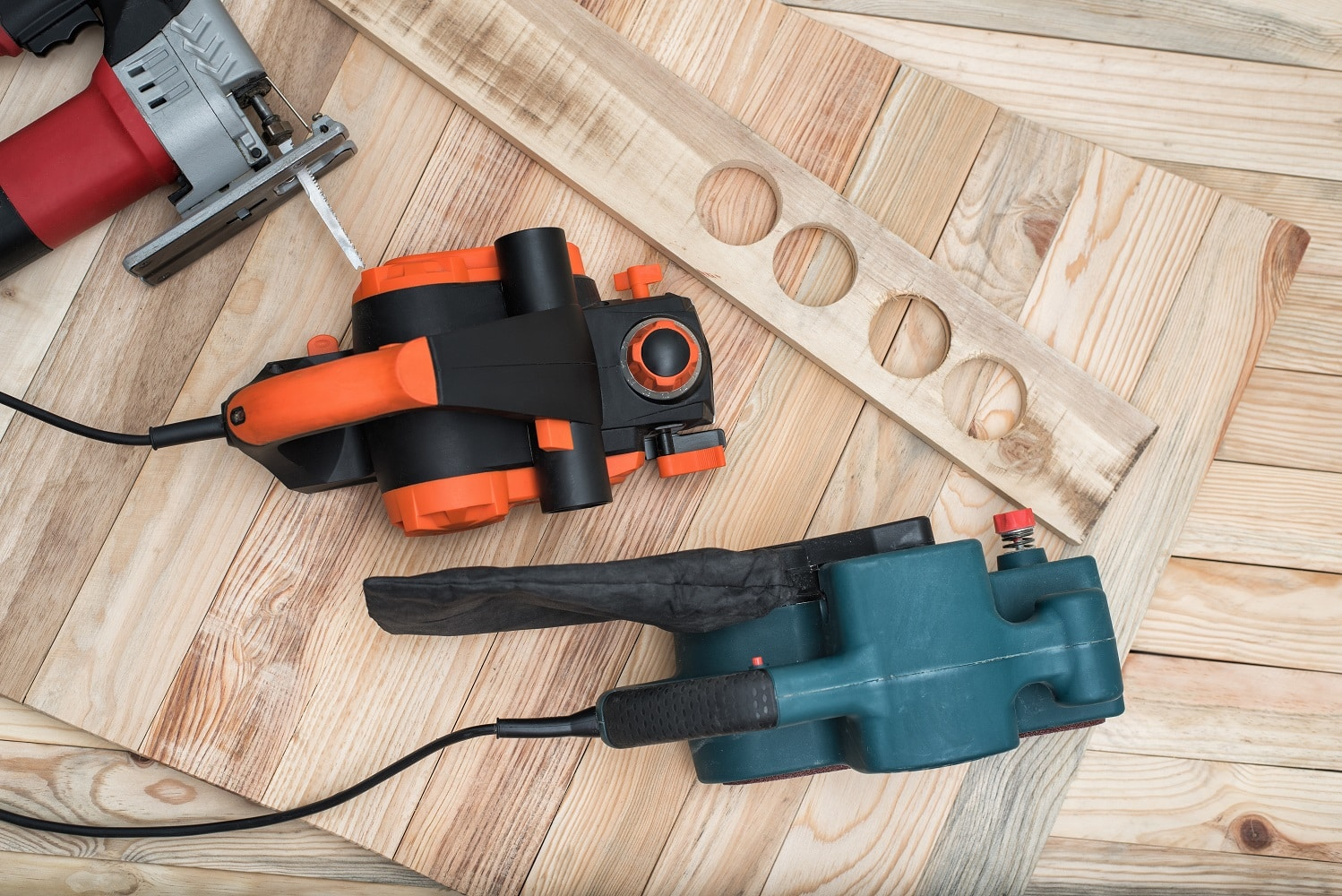 Set of handheld woodworking power tools for woodworking and the workpiece lies on a light wooden background
