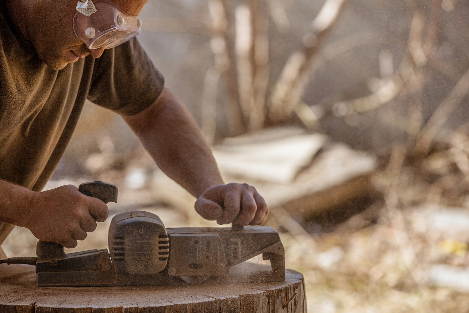 Carpenter working with electric planer on wooden stump in the open air, wearing goggles.