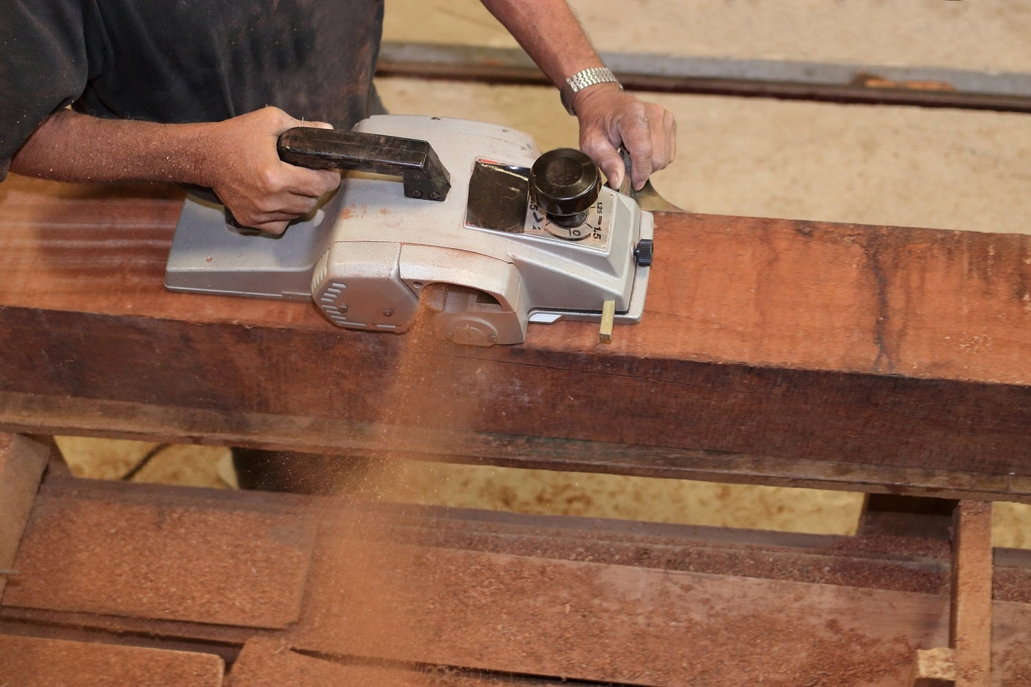 Aerial view of senior carpenter using electric planer on a piece of wood in carpentry workshop. Selective focus and shallow depth of field.